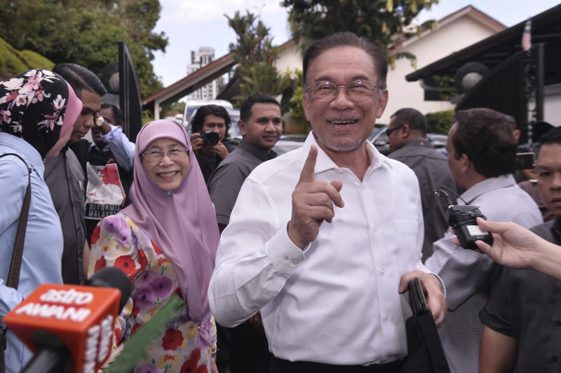 Politician Anwar Ibrahim, right, gestures next to his wife Wan Azizah Ismail as they head to their party headquarters after meeting the king in Kuala Lumpur, Malaysia, Wednesday, Feb. 26, 2020. Malaysia's king held unusual consultations with lawmakers for a second day Wednesday to resolve a political vacuum caused by the abrupt collapse of the ruling coalition and the resignation of Prime Minister Mahathir Mohamad. (AP Photo)
