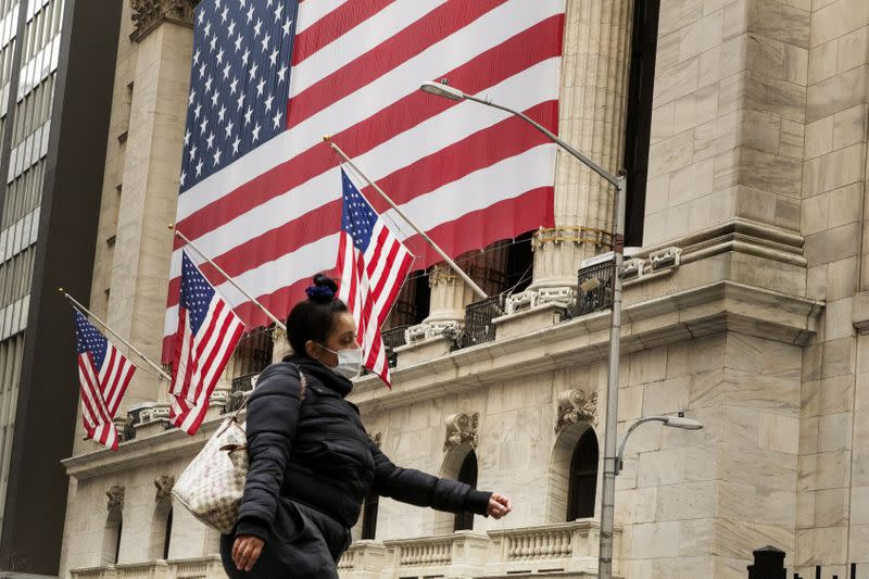 FILE PHOTO: A pedestrian with a mask walks past of the NYSE as markets continue to react to the coronavirus disease (COVID-19) at the NYSE in New York