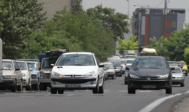 Iranians drive locally-manufactured Peugeot 206 cars in the streets of Tehran on July 24, 2012 (AFP Photo/Atta Kenare)