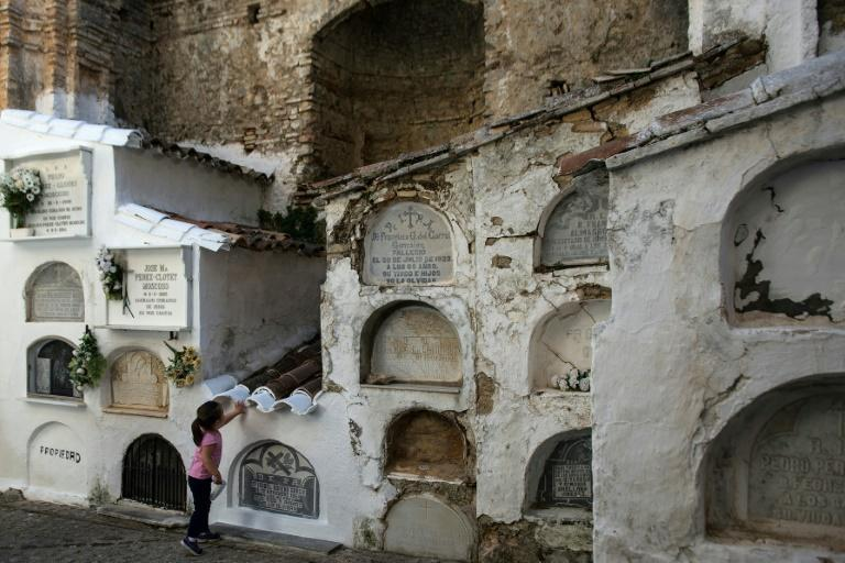 A girl touches a grave at Villaluenga del Rosario near Cadiz -- but amid spiking coronavirus cases authorities have urged Spaniards to space out All Saints Day visits to pay respects