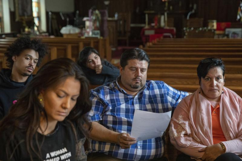 In this Wednesday, June 19, 2019 photo, attorney Roberto Lopez, center, of the Law Office of Schiller Pryer and pastor Jacobita Cortes from Adalberto Methodist Church participate in an emergency meeting plan of action on how to defend and protect undocumented communities of deportation at Lincoln Methodist Church in Chicago's Pilsen neighborhood.  With renewed pledges on mass deportations, immigrant rights activists have fine-tuned and ramped up one of their most basic organizing tools: The know-your-rights training. (AP Photo/Amr Alfiky)