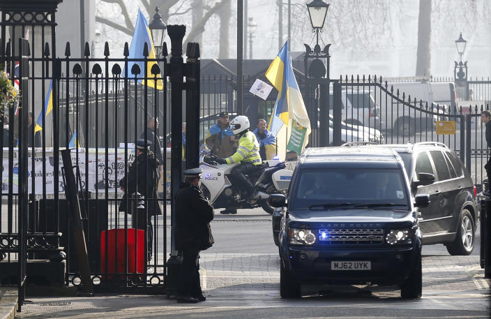 The convoy of cars carrying US Secretary of State John Kerry drives past a small Ukraine demonstration as he arrives for a meeting with Britain's Prime Minister David Cameron and the Foreign Secretary William Hague at Downing street in London, Friday, March, 14, 2014. Kerry arrived in London Friday, for his last meeting with Russian Foreign Minister Sergey Lavrov before the Crimea vote. (AP Photo/Sang Tan)