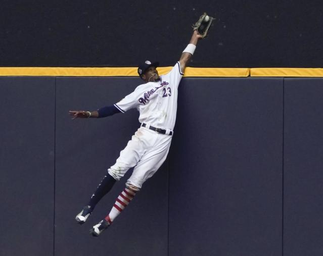 FILE - In this July 4, 2018, file photo, Milwaukee Brewers' Keon Broxton makes a leaping catch at the wall on a ball hit by Minnesota Twins' Brian Dozier during the ninth inning of a baseball game in Milwaukee. The New York Mets acquired Broxton from the Brewers on Saturday, Jan. 5, 2019, giving them a center field option in addition to Juan Lagares. (AP Photo/Morry Gash, File)