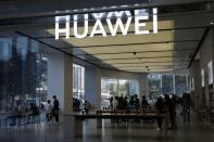 People are seen inside a Huawei store at a shopping mall in Beijing