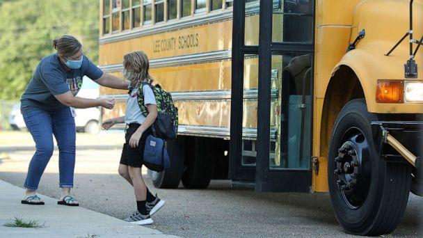 PHOTO: Audrey Wylie, a speech pathologist, at Saltillo Primary School, puts a bus number sticker on Cruz Antle, a first grader, as he gets off the bus for his first day back to school, Aug. 6, 2020, in Saltillo, Miss.  (Adam Robison/The Northeast Mississippi Daily Journal via AP)
