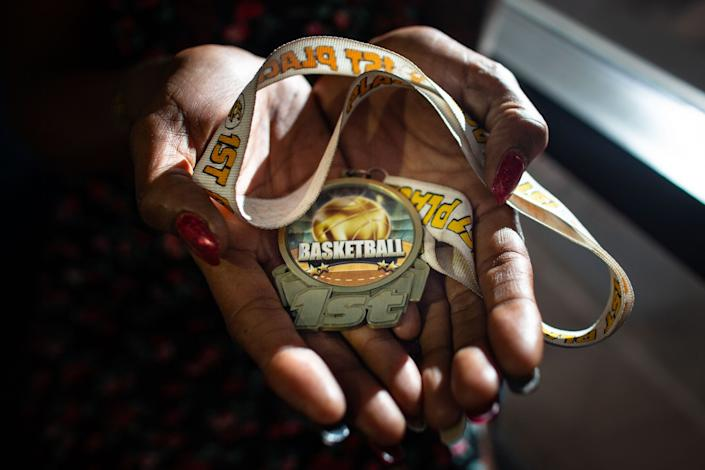 """Taloma Miller holds one of her son's basketball medals. <span class=""""copyright"""">(Jason Armond / Los Angeles Times)</span>"""