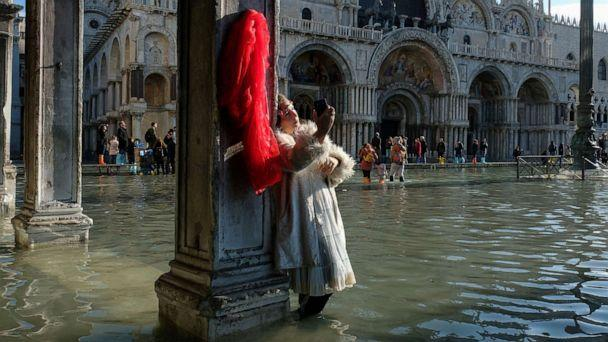 PHOTO: A woman takes pictures in the flooded St. Mark's Square during a period of seasonal high water in Venice, Italy, Nov. 14, 2019. (Manuel Silvestri/Reuters)