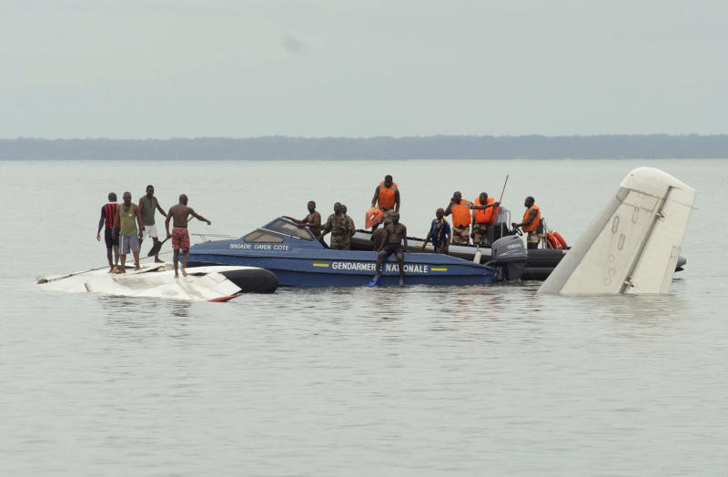 Military police investigate a partially-submerged DHL cargo plane, which crashed just off the coast of Libreville, Gabon, Monday, June 6, 2011. The plane went down Monday morning, coming to rest with its nose buried in the low tide just off the coast near a major high school. Authorities at the scene who asked not to be named because they are not authorized to speak to the press said the four-man crew had survived and had been taken to a local hospital. (AP Photo/Joel Bouopda Tatou)