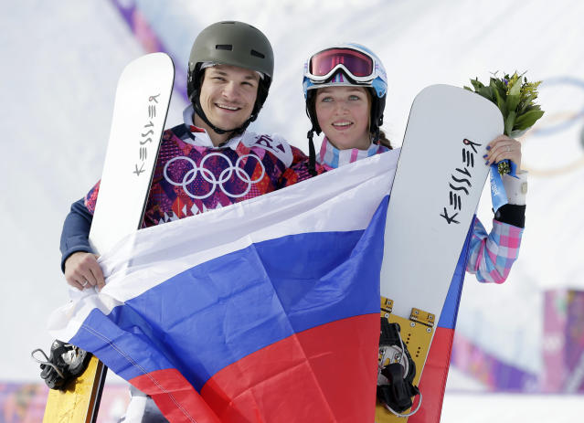 Russia's Vic Wild, left, poses after winning the gold medal in the men's snowboard parallel giant slalom final, with his wife and bronze medalist in the women's snowboard parallel giant slalom final, Russia's Alena Zavarzina, at the Rosa Khutor Extreme Park, at the 2014 Winter Olympics, Wednesday, Feb. 19, 2014, in Krasnaya Polyana, Russia. (AP Photo/Andy Wong)