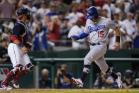 Los Angeles Dodgers' Austin Barnes, right, scores on a single by Mookie Betts during the seventh inning of a baseball game against the Washington Nationals, Friday, July 2, 2021, in Washington. Nationals' Yan Gomes, left, looks on. (AP Photo/Julio Cortez)