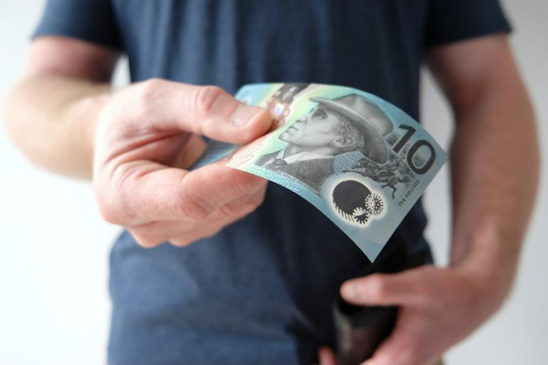 A man handing out ten Australian dollar note. A picture that describes buying, paying, handing out money, or showing money.