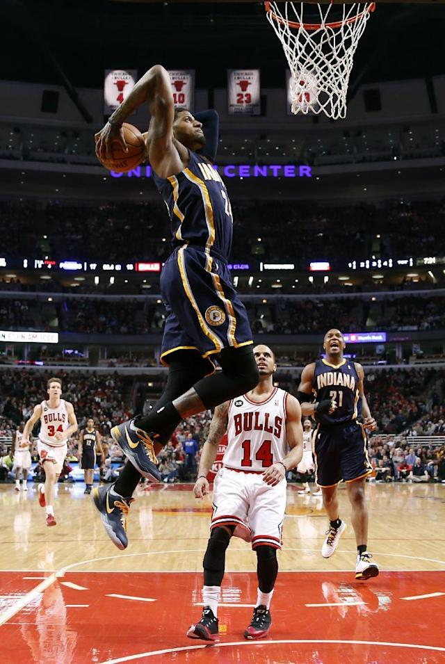 Indiana Pacers forward Paul George dunks the ball over Chicago Bulls guard D.J. Augustin (14) as David West (21) watches during the first half of an NBA basketball game Monday, March 24, 2014, in Chicago. (AP Photo/Charles Rex Arbogast)