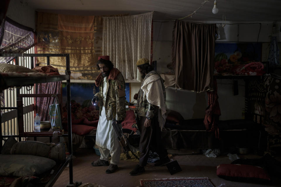 Taliban fighters walk inside an empty cell at the Pul-e-Charkhi prison in Kabul, Afghanistan, Monday, Sept. 13, 2021. Pul-e-Charkhi was previously the main government prison for holding captured Taliban and was long notorious for abuses, poor conditions and severe overcrowding with thousands of prisoners. Now after their takeover of the country, the Taliban control it and are getting it back up and running, current holding around 60 people, mainly drug addicts and accused criminals. (AP Photo/Felipe Dana)