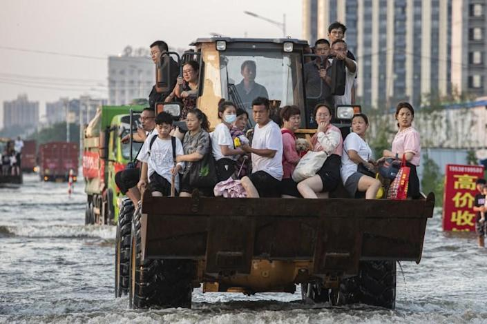 Trucks and bulldozers turn to be vehicles for the victims to evacuate their homes in Weihui city.