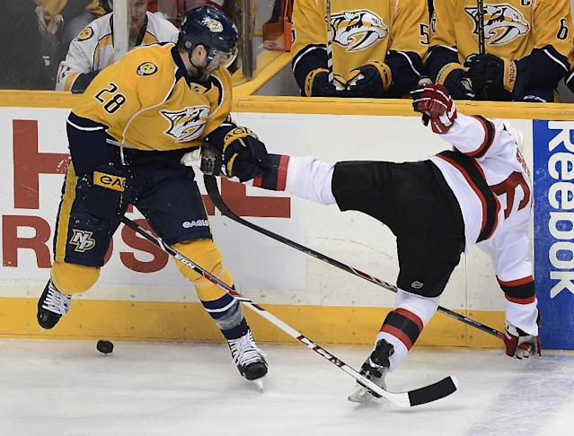 Nashville Predators forward Paul Gaustad (28) checks New Jersey Devils defenseman Andy Greene (6) into the boards while trying to get control of the puck in the first period of an NHL hockey game on Friday, Jan. 31, 2014, in Nashville, Tenn. (AP Photo/Mark Zaleski)