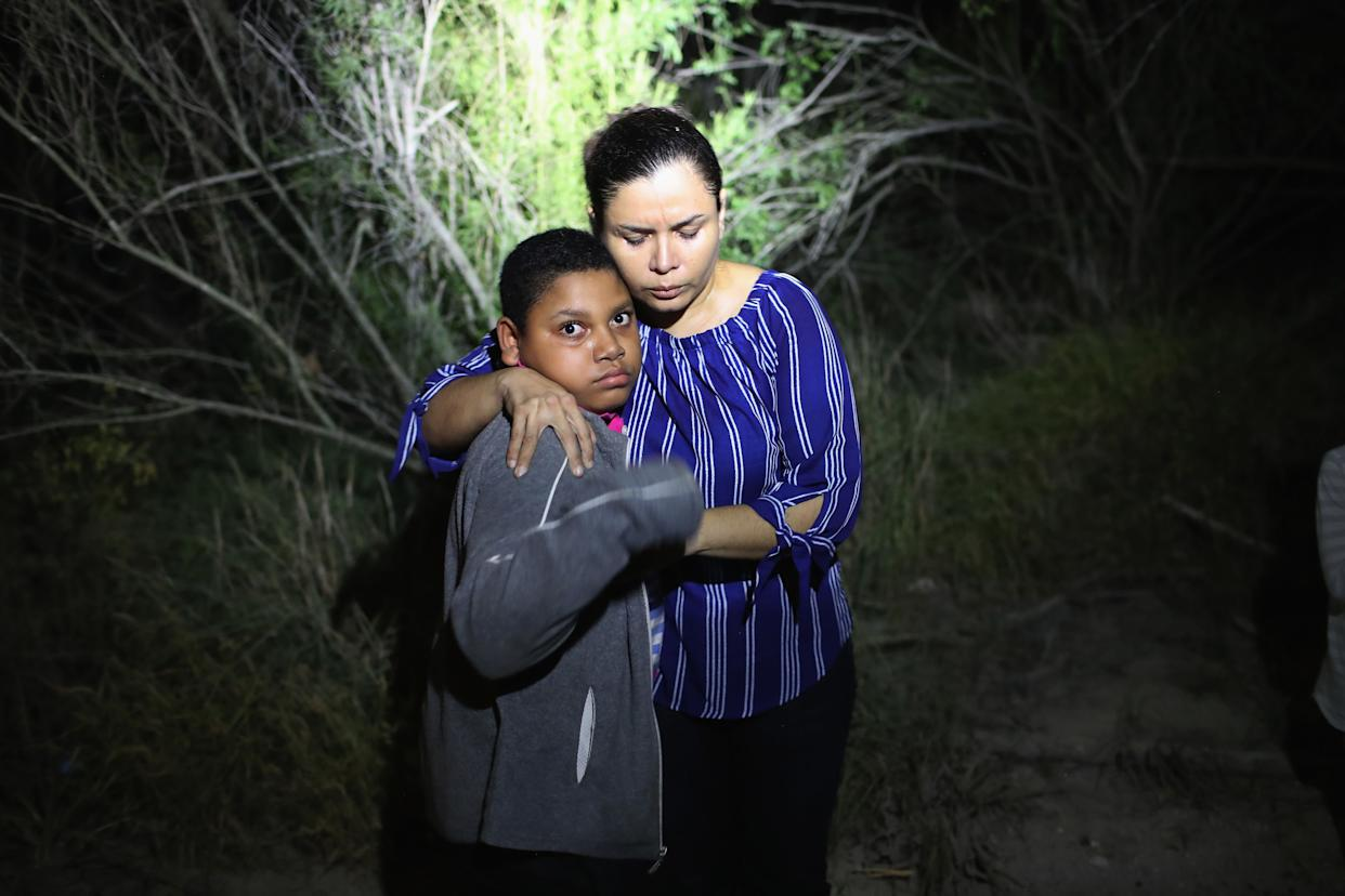 A U.S. Border Patrol spotlight shines on a mother and son from Honduras on June 12, 2018, in McAllen, Texas.