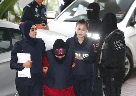 Indonesian Siti Aisyah, who is on trial for the killing of Kim Jong Nam, the estranged half-brother of North Korea's leader, is escorted as she arrives at the Shah Alam High Court on the outskirts of Kuala Lumpur, Malaysia January 22, 2018. REUTERS/Lai Seng Sin