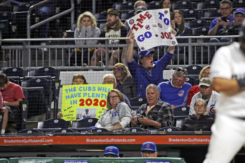 A Chicago Cubs fan holds a sign as Cubs manager Joe Maddon, bottom right, stands in the dugout during the ninth inning of the team's baseball game against the Pittsburgh Pirates in Pittsburgh, Thursday, Sept. 26, 2019. The Pirates won 9-5. (AP Photo/Gene J. Puskar)