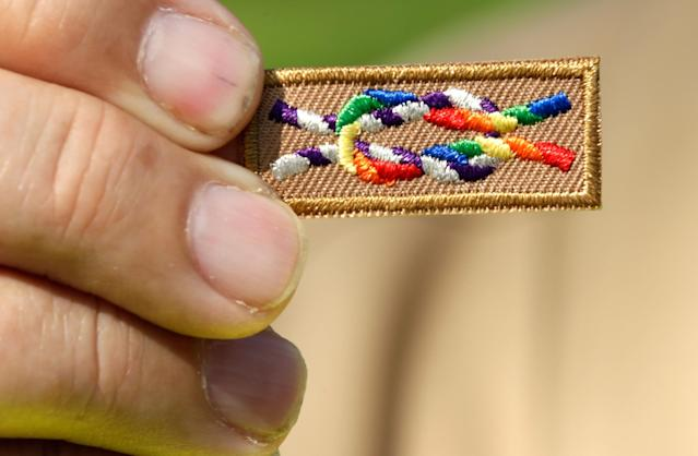 "WASHINGTON, DC - MAY 22: A member of Scouts for Equality holds an unofficial knot patch incorportating the colors of the rainbow, a symbol for gay rights, during a rally to call for equality and inclusion for gays in the Boy Scouts of America as part of the ""Scouts for Equality Day of Action"" May 22, 2013 in Washington, DC. The Boy Scouts of America is scheduled to hold a two day meeting tomorrow with 1,400 local adult leaders to consider changing its policy of barring openly gay teens from participating in the Boy Scouts. (Photo by Win McNamee/Getty Images)"