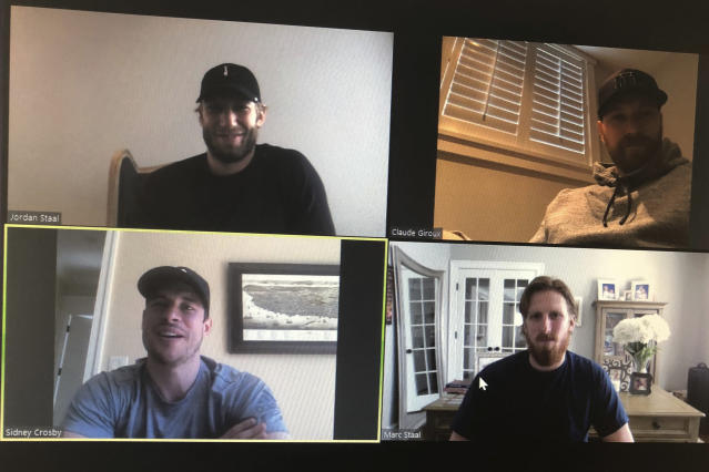 NHL hockey players Jordan Staal, captain of the Carolina Hurricanes, clockwise from top left, Claude Giroux, captain of the Philadelphia Flyers, Marc Stall, alternate captain for the New York Rangers and Sidney Crosby, captain of the Pittsburgh Penguins, take part in an NHL video call with players representing the Metropolitan Division Thursday, March 26, 2020, in this photo made in Buffalo, N.Y. (AP Photo/John Wawrow)