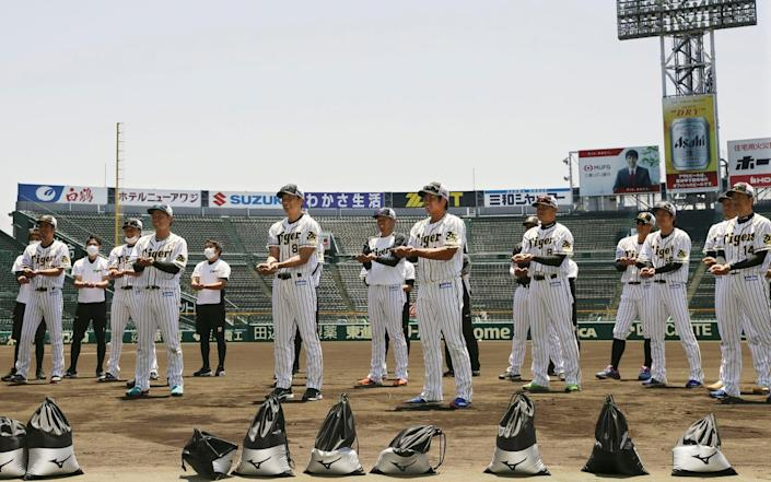 Players of the Japanese professional baseball team Hanshin Tigers show dirt they collected from the grounds of Koshien Stadium in Nishinomiya, western Japan, on Tuesday - Yohei Fukuyama/Kyodo News