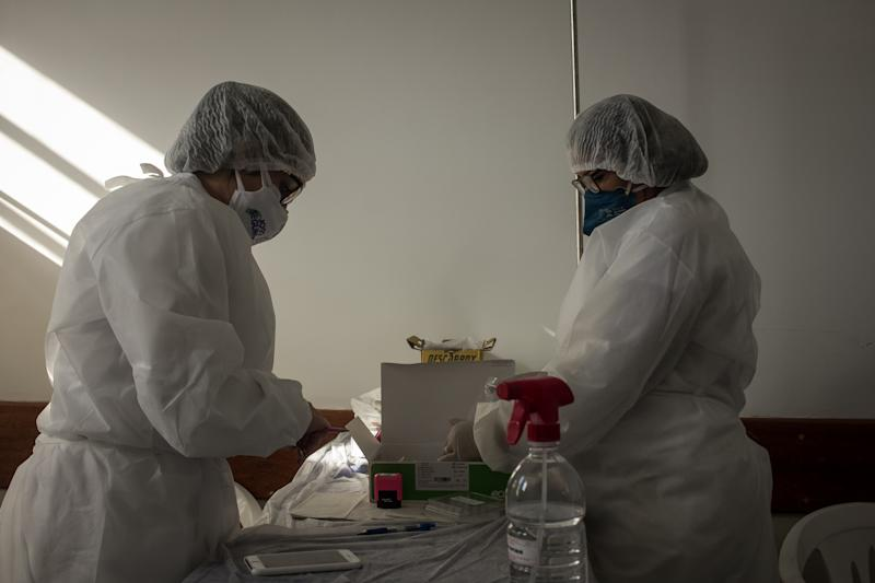 Nurses wearing protective masks written ''Safe Game'' perform tests for COVID-19 (coronavirus) before the start of the match between Fluminense and Botafogo valid for the Rio Car Cup 2020 Rio Cup semi-final that takes place at the Nilton Santos Stadium (Engenhao) located in the North Zone from Rio de Janeiro, Brazil, on July 5, 2020. The games of the Rio championship take place during the period of social isolation (quarantine) and take place without the presence of an audience (fans). (Photo by Allan Carvalho/NurPhoto via Getty Images)