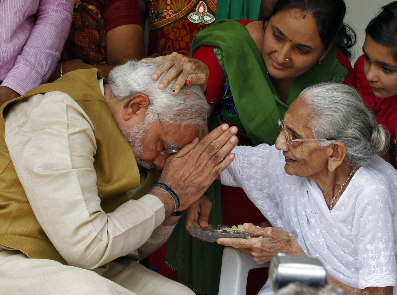 Hindu nationalist Narendra Modi (L), the prime ministerial candidate for India's main opposition Bharatiya Janata Party (BJP), seeks blessings from his mother Heeraben at her residence in Gandhinagar in the western Indian state of Gujarat May 16, 2014. Modi will be the next prime minister of India, with counting trends showing the pro-business Hindu nationalist and his party headed for the most resounding election victory the country has seen in thirty years. REUTERS/Amit Dave (INDIA - Tags: POLITICS ELECTIONS TPX IMAGES OF THE DAY)