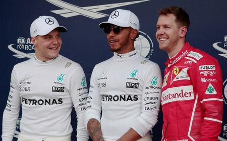 Formula One - F1 - Australian Grand Prix - Melbourne, Australia - 25/03/2017 Mercedes driver Lewis Hamilton (C) of Britain reacts after setting pole position in qualifying alongside team mate Valtteri Bottas (L) of Finland and Ferrari's Sebastian Vettel of Germany. REUTERS/Jason Reed