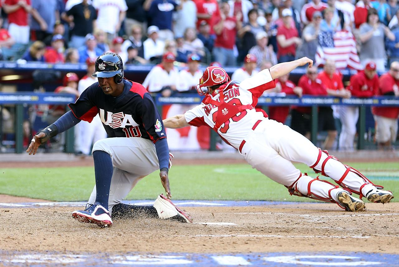PHOENIX, AZ - MARCH 10:  Adam Jones #10 of USA scores a run past catcher Chris Robinson #30 of Canada during the eighth inning of the World Baseball Classic First Round Group D game at Chase Field on March 10, 2013 in Phoenix, Arizona.  (Photo by Christian Petersen/Getty Images)