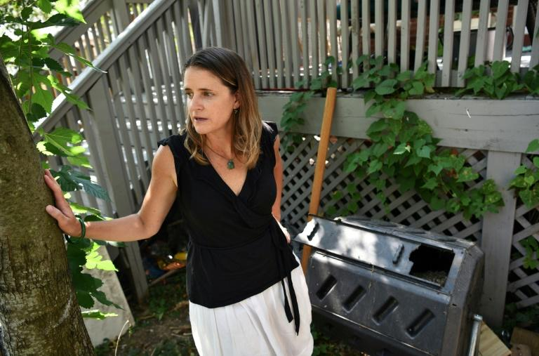 Elizabeth Hogan stands next to a composter as she speaks during an interview about her efforts to lower her carbon footprint at her home in Washington (AFP Photo/MANDEL NGAN)