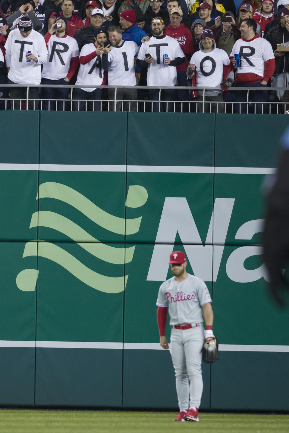 Fans let their feelings be known for Philadelphia Phillies right fielder Bryce Harper, bottom, in the first inning of a baseball game against the Washington Nationals at Nationals Park, Tuesday, April 2, 2019, in Washington. (AP Photo/Alex Brandon)