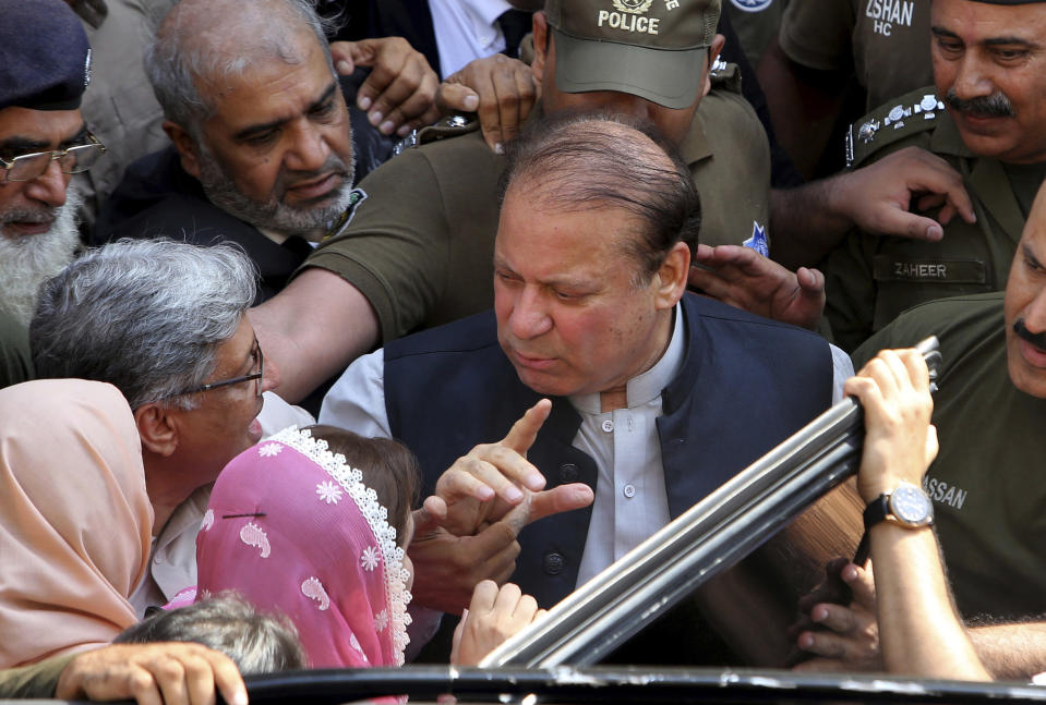 FILE - In this Oct. 11, 2019 file photo, former Prime Minister Nawaz Sharif arrives at a court in Lahore, Pakistan. Pakistan's information minister says Islamabad has started a legal process, Friday, Dec. 18, 2020, to reach an extradition treaty with Britain that would pave the way for the U.K. to hand over Sharif. The development comes after a top Pakistani court earlier this month declared Sharif, who lives in self-imposed exile in London, a fugitive from justice for failing to return home to face additional corruption charges. (AP Photo/K.M. Chaudary)