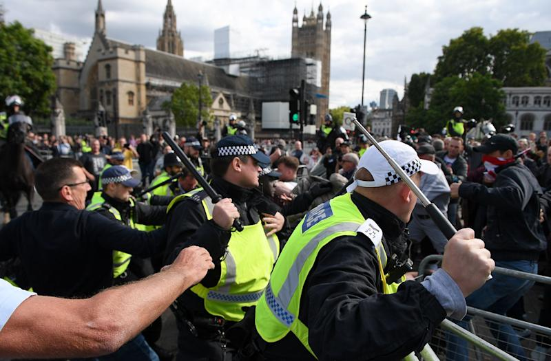Demonstrators remonstrate with police officers on Parliament Square.