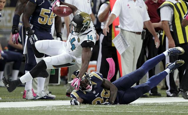Jacksonville Jaguars wide receiver Justin Blackmon (14) runs with the ball before being knocked down by St. Louis Rams safety Darian Stewart, right, during the first quarter of an NFL football game Sunday, Oct. 6, 2013, in St. Louis. (AP Photo/Tom Gannam)