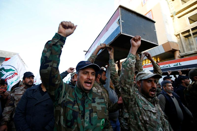 Hashd al-Shaabi (paramilitary forces) fighters carry coffins of members of Kataib Hezbollah militia group, who were killed by U.S. air strikes in Qaim district, during a funeral in the holy city of Najaf, Iraq December 31, 2019. REUTERS/Alaa al-Marjani