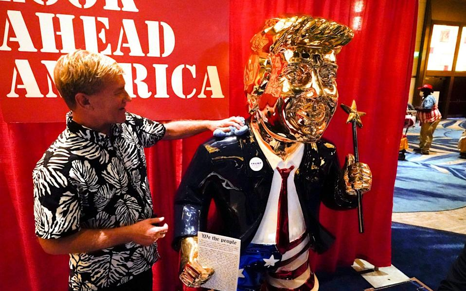 A gold-plated statue of Donald Trump was unveiled at the conference - AP