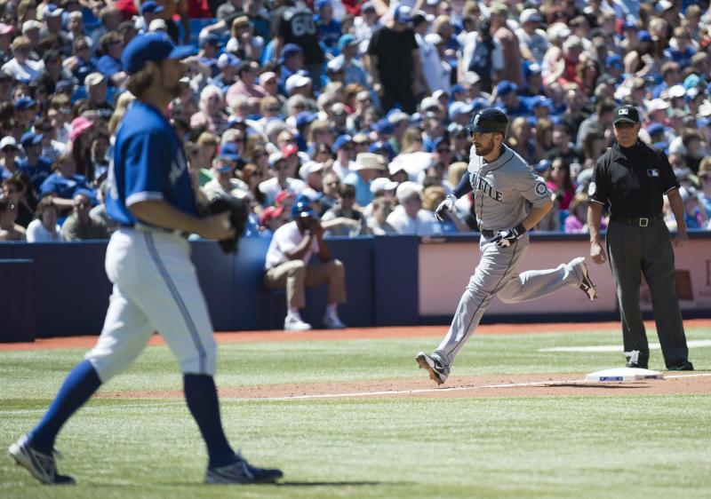 Seattle Mariners second baseman Dustin Ackley, right, rounds the bases past Toronto Blue Jays pitcher R.A. Dickey, left, after hitting a grand slam during the fourth inning of a baseball game in Toronto on Saturday, May 4, 2013. (AP Photo/The Canadian Press, Nathan Denette)