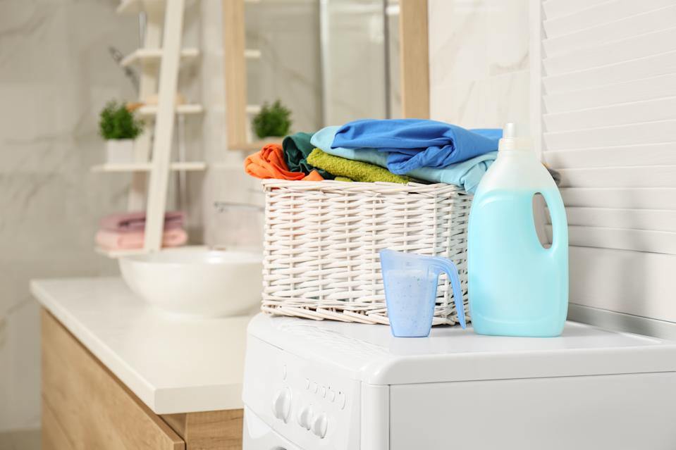 Wicker basket with laundry and detergents on washing machine in bathroom