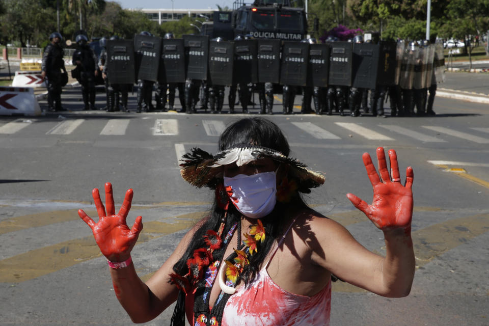 An Indigenous woman stands in front of a formation of riot police blocking a road, outside Congress in Brasilia, Brazil, Tuesday, June 22, 2021. Indigenous are camping in the capital to oppose a proposed bill they say would limit recognition of reservation lands. (AP Photo/Eraldo Peres)