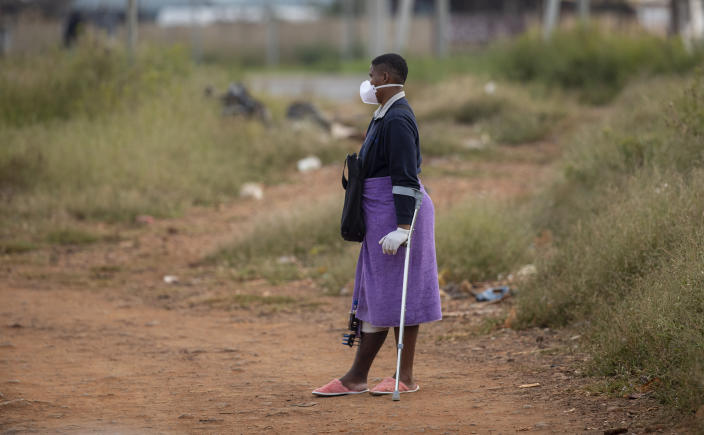 Noxolo Mbatha, wearing face masks and surgical gloves to protect herself against coronavirus, awaits a taxi for her hospital appointment at a informal settlement, east of Johannesburg, South Africa, Friday, March 27, 2020. The new coronavirus causes mild or moderate symptoms for most people, but for some, especially older adults and people with existing health problems, it can cause more severe illness or death. (AP Photo/Themba Hadebe)