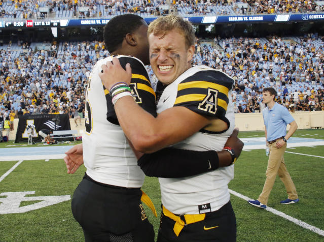Appalachian State's David Baldwin-Griffin, left, and Thomas Hennigan, right, celebrate after the team pulled an upset win over North Carolina in an NCAA college football game in Chapel Hill, N.C., Saturday, Sept. 21, 2019. (AP Photo/Chris Seward)
