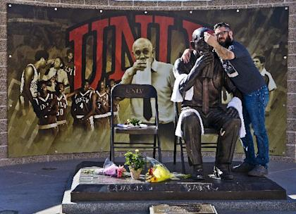 """UNLV alumnus Taylor Oblad takes a """"selfie"""" at the Jerry Tarkanian statue near the Thomas & Mack Center in Las Vegas, Wednesday, Feb. 11, 2015. Hall of Fame coach Jerry Tarkanian, who built a basketball dynasty at UNLV but was defined more by his decades-long battle with the NCAA, died Wednesday, Feb. 11, 2015, in Las Vegas after several years of health issues. He was 84.(AP Photo/The Sunm L.E. Baskow)"""