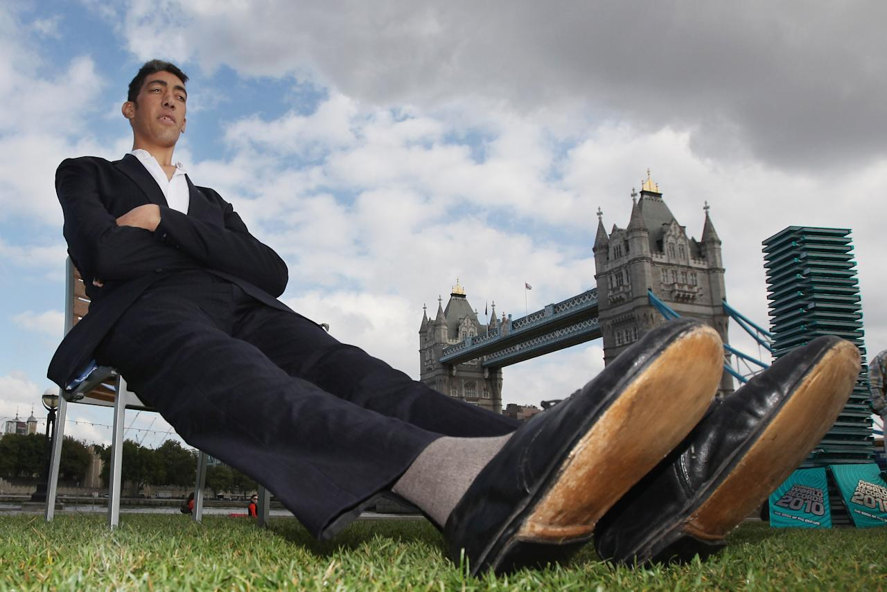 LONDON, ENGLAND - SEPTEMBER 16:  (EMBARGOED UNTIL 00.01AM ON SEPTEMBER 17) The worlds new tallest man Sultan Kosen 26, of Turkey poses in front of Tower Bridge to celebrate the launch of the 2010 Guinness Book of Records, on September 16, 2009 in London, England. Sultan Kosen stands at 8ft 1in and also holds the record for the largest hands and largest feet at 27.5cm and 36.5cm respectively.  (Photo by Dan Kitwood/Getty Images)