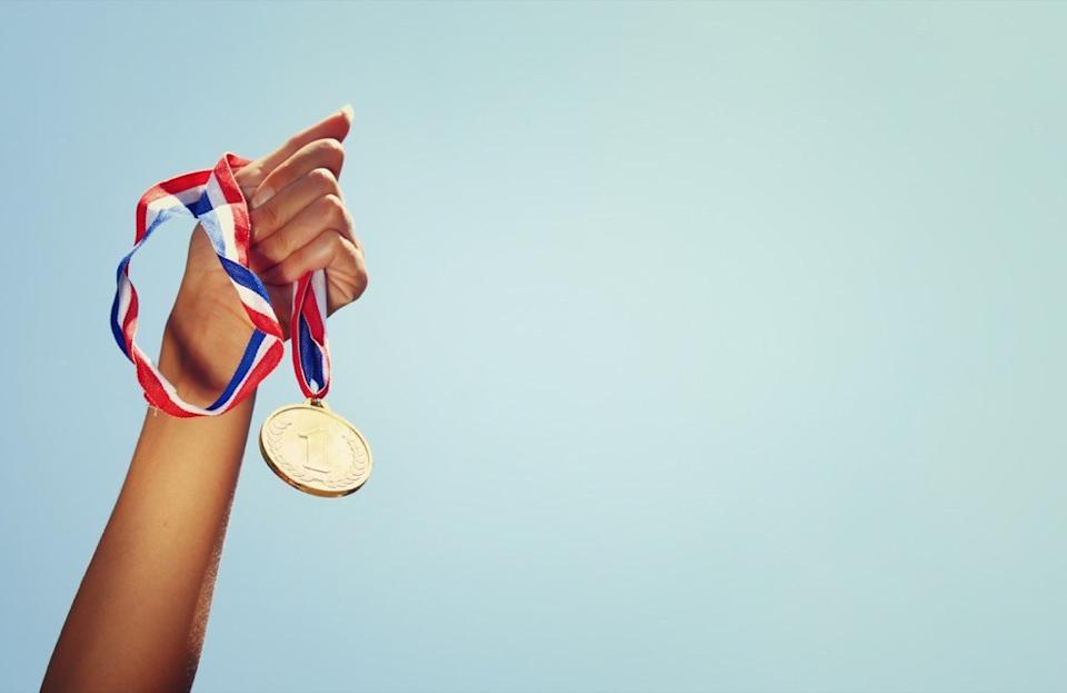 Woman at the Olympics holding a gold medal