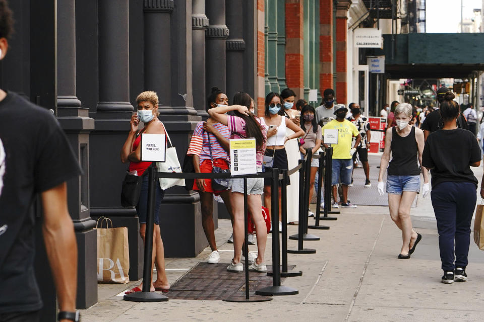 Photo by: John Nacion/STAR MAX/IPx 2020 6/26/20 People wait in line to get into a department store in SoHo as Manhattan enters Phase 2 of re-opening following restrictions imposed to curb the coronavirus pandemic on June 26, 2020 in New York City. Phase 2 permits the reopening of offices, in-store retail, outdoor dining, barbers and beauty parlors and numerous other businesses. Phase 2 is the second of four-phased stages designated by the state.