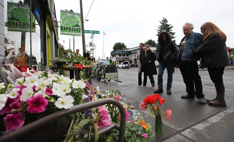 Friends and neighbors stand at the scene of where a gunman killed four people and severely wounded another in a cafe a day earlier, Thursday, May 31, 2012, in Seattle. Police say the assailant later killed a woman during a carjacking before shooting himself. As officers closed in during a widespread manhunt on Wednesday, the suspect put a gun to his head and pulled the trigger and later died at a hospital. (AP Photo/Elaine Thompson)
