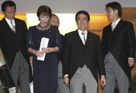 Japanese Prime Minister Shinzo Abe (2nd R) smiles as he leads then Foreign Minister Taro Aso (L), Gender Equality Minister Sanae Takaichi (2nd L), Justice Minister Jinen Nagase (3rd L) and Chief Cabinet Secretary Yasuhisa Shiozaki (R) during a photo session at the premier's official residence in Tokyo, in this September 26, 2006 file photo. REUTERS/Toru Hanai/Files