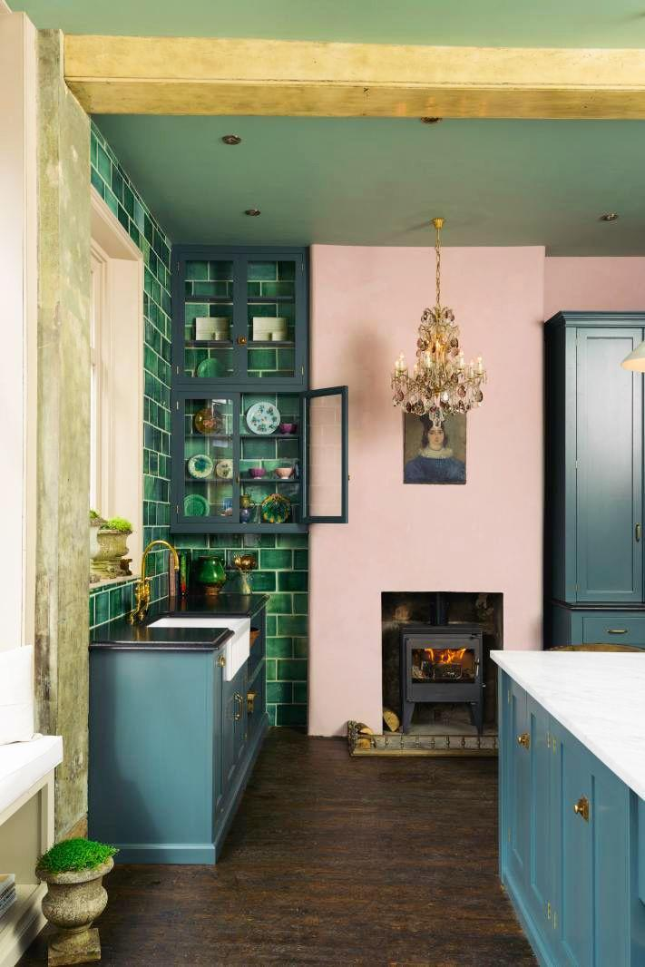 <p>This retro-inspired deVOL kitchen is a beautiful blend of classic English design with contemporary functionality. The glass cabinet customized to fit right into the corner and looks beautiful with the baby pink paint and Kelly green backsplash. And of course, that wood-burning fireplace drives home the charm. </p>