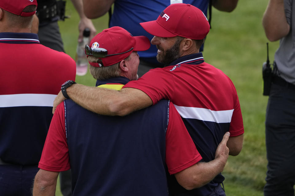 Team USA captain Steve Stricker hugs Team USA's Dustin Johnson after a Ryder Cup singles match at the Whistling Straits Golf Course Sunday, Sept. 26, 2021, in Sheboygan, Wis. (AP Photo/Jeff Roberson)