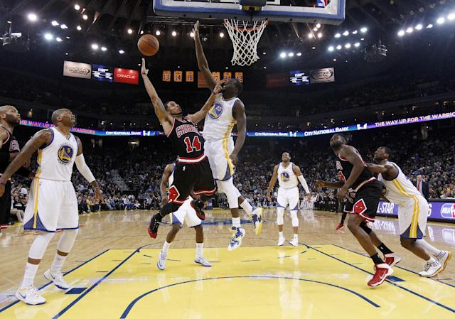 Chicago Bulls' D.J. Augustin (14) releases a shot as Golden State Warriors' Draymond Green (23) defends during the first half of an NBA basketball game Thursday, Feb. 6, 2014, in Oakland, Calif. (AP Photo/Marcio Jose Sanchez)